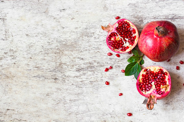 half pomegranate and ripe pomegranate fruit on white wooden rustic background