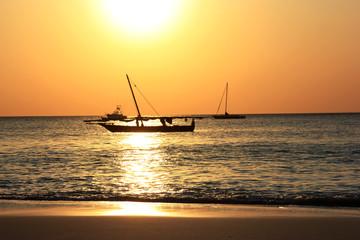 Традиционная рыбацкая лодка Доу, в открытом океане на фоне заката. Занзибар, Танзания.