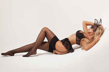 Stylish sexy blonde girl in a black lingerie and with stockings and garters isolated on a white background