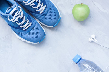 Flat lay sport shoes, bottle of water and earphones