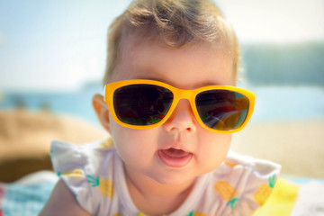 Close up of a baby girl wearing yellow sunglasses at the beach.