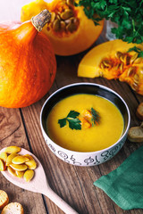 Cream pumpkin soup with fresh herbs and crackers on dark wooden background. Healthy food. Selective focus. Top view.