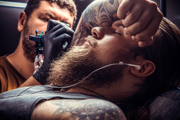 Professional tattooer at work in tattoo parlor