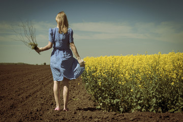 Rear view of lonely Caucasian woman in canola field holding flow