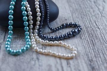 Trois colliers de perles avec galet noir sur bois gris
