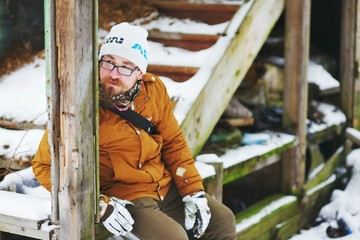 Young bearded man in glasses sitting on the steps of the old wooden stairs in the winter, closeup.