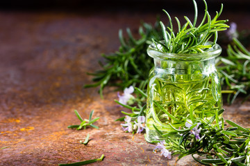 Rosemary essential oil jar glass bottle and branches of plant