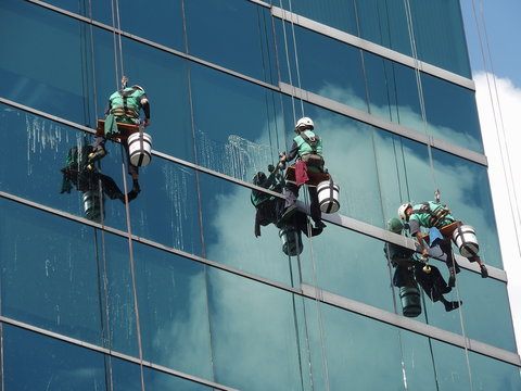 men cleaning glass building by rope access at height