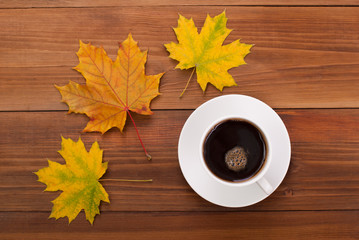 Cup of coffee and maple leaves on a wooden table.