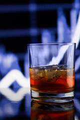 Whiskey glass with ice against blue blurred background