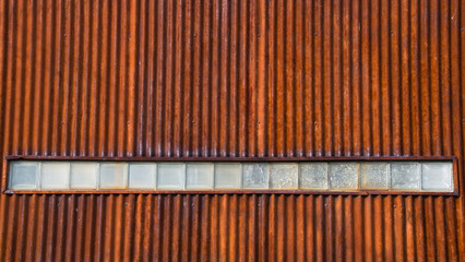 Rusty, Corrugated Metal Wall with a Row of Textured Glass Blocks