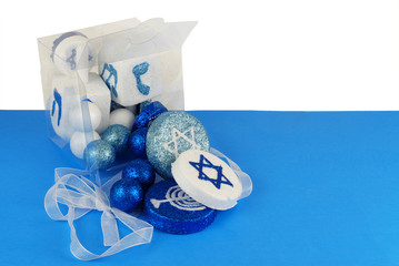 Sparkling Hanuakkah decorationsspilling out of a clear plastic gift box tied with a white ribbon on a blue and white background. Copy space right side.