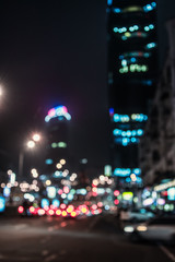 Blurred glowing skyscrapers and cars. Night city street  lights