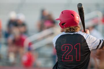 High school baseball player with long hair batting.