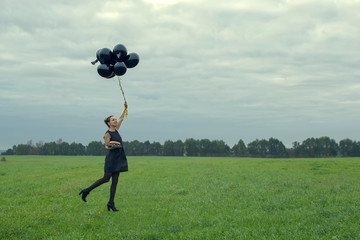 Fashion girl with ballons jumping