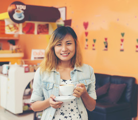 Portrait of young beautiful woman sitting in a cafe  holding hot