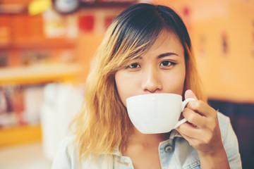 Young beautiful woman drinking hot cappuccino coffee at cafe.