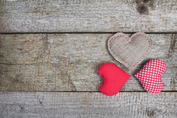 Three handmade hearts on wooden rustic background