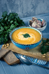 cream soup with pumpkin, greens, seeds and bread on a blue backg