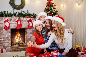 Beautiful girls, friends in caps of Santa Claus doing selfie mob