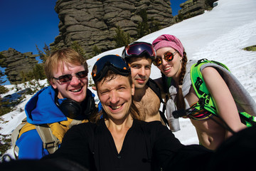 Group of happy friends snowboarding doing selfie