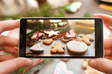 Christmas traditional treat photography on phone. Taking a picture of gingerbread cookies variety. Food photography, Instagram, culinary concept