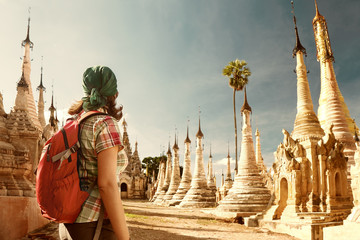 Woman traveling  with backpack and looks at Buddhist stupas