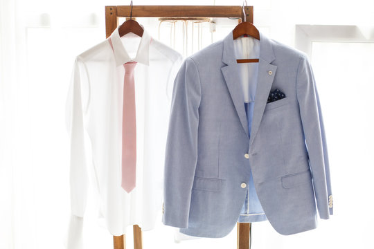 White shirt and gray suit of groom hanging on hanger