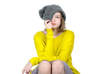 Portrait of a cute teen girl, who pulls his cap over her face..