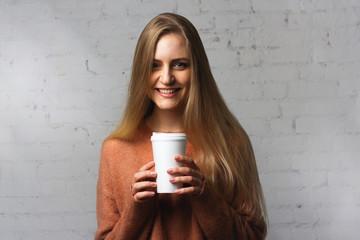 Joyful girl poses with a coffee cup.