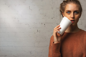 Portrait of surprised beautiful girl with a cup of coffee in hand. Eyes wide open