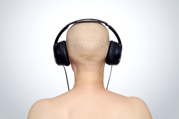 Bald female head with headphones, rear view. File contains a path to isolation.