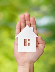 Hand holding white paper house figure on green background