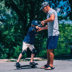 Skateboarding in park. Little boy trying snakeboard with grandpa