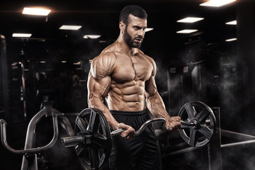 Handsome man with big muscles, posing at the camera in the gym Fototapete