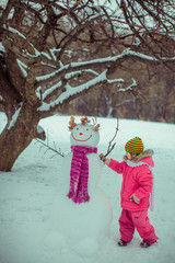 Girl is playing with the snowman  in the winter