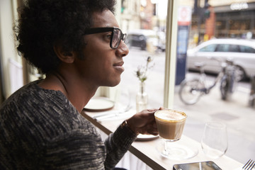 Young man looking through window while having coffee in cafe