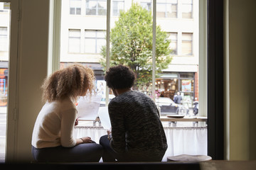 Rear view of young couple looking at menus in restaurant