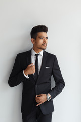 Making business look good. Confident young man in formal wear looking away while standing against grey background