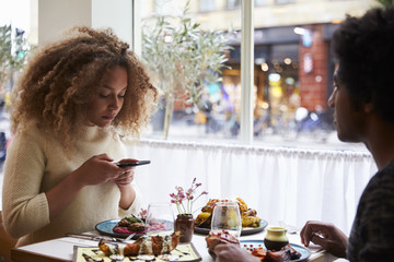 Young woman taking picture of meal in restaurant on mobile