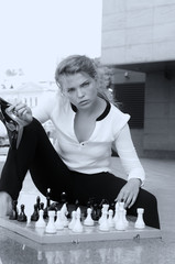 Girl makes a move on the chessboard