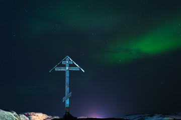 A large wooden cross on a background of aurora
