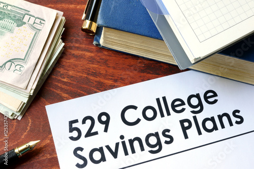 Papers with 529 college savings plans on a table stock for 528 plan