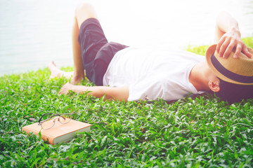man's face covered by hat lying down on grass resting by lake side with a book at his side
