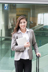 beautiful asian young girl with tablet and luggage