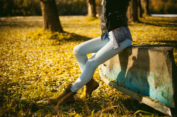 slim girl's legs in blue jeans and brown boots. girl sat on the upturned boat, on the shore, yellow autumn leaves