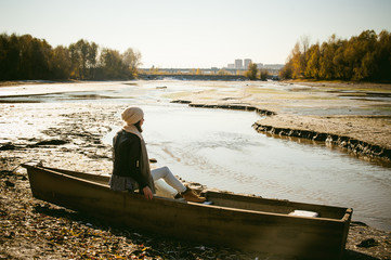 Slim girl in blue jeans, brown jacket and boots, sat on the upturned boat, on the shore, yellow autumn leaves bright sunny day