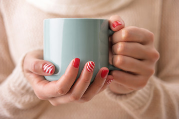 Women's hands holding a cup of drink.