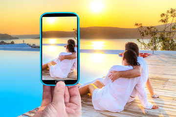 Making photos by smartphone of loving couple at sunset
