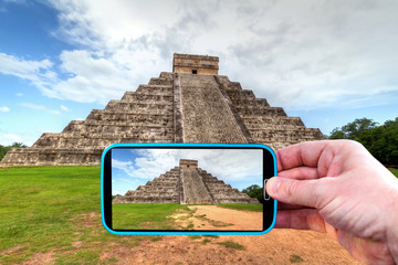 Making photos by smartphone of pyramid in Chichen Itza, Mexico